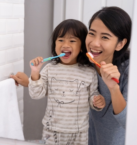 Mother and child brushing teeth to prevent dental emergencies