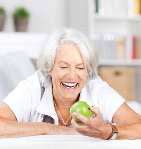 Senior woman enjoying apple with help of dental dental implant-retained dentures