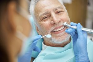 a person sitting in a treatment chair having their dental implants in Plano professionally cleaned